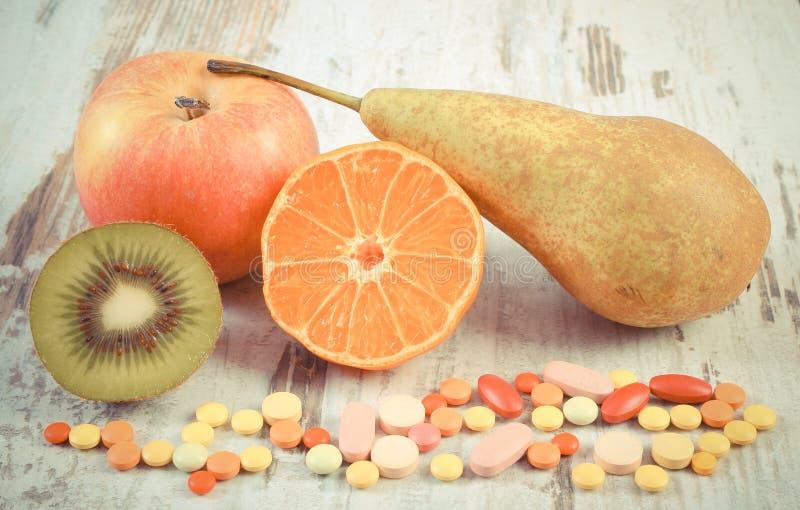 Weinlesefoto, frische Früchte und bunte medizinische Pillen, Wahl zwischen gesunder Nahrung und medizinischen Ergänzungen stockfotografie