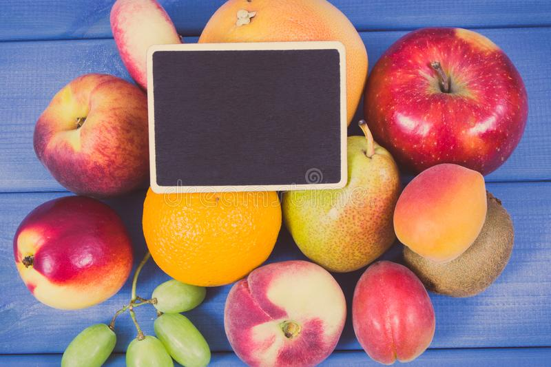 Weinlesefoto, frische natürliche Früchte, die nahrhafte Vitamine und schwarzes Brett für Text, gesundes Lebensstilkonzept enthalt lizenzfreies stockfoto