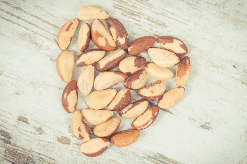 Weinlesefoto, Haufen von Paranüssen in Form des Herzens, gesundes Lebensmittel, das natürliche Mineralien enthält stockbild