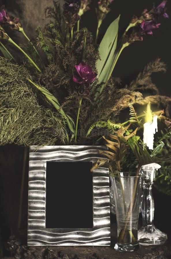Weinlesefotorahmen und -blumen auf Holztisch über Schmutzhintergrund-Stilllebenart stockbilder