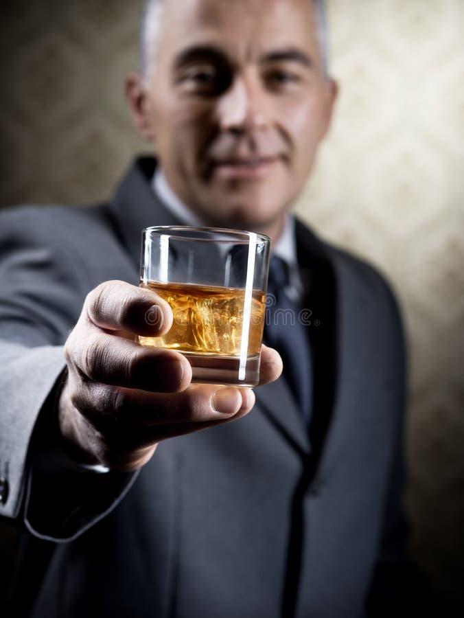 Weinlesegeschäftsmann, der ein Glas Whisky hält stockbild