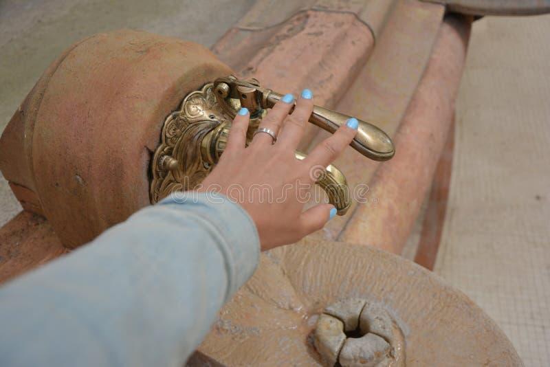 Weinlesehahn mit einer Quelle des Mineralwassers und der Hand der Frauen lizenzfreies stockfoto