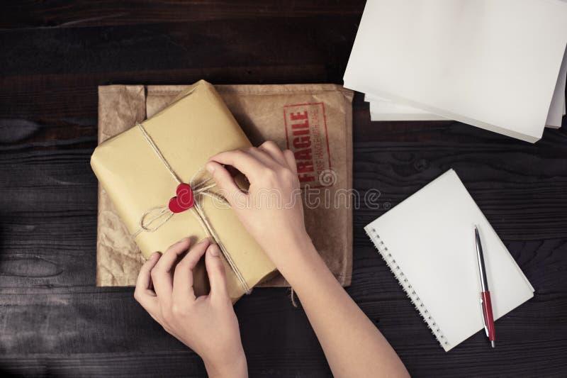 Weinlesehandwerks-Pappgeschenkbox mit rotem Herzen auf Holztisch stockfoto