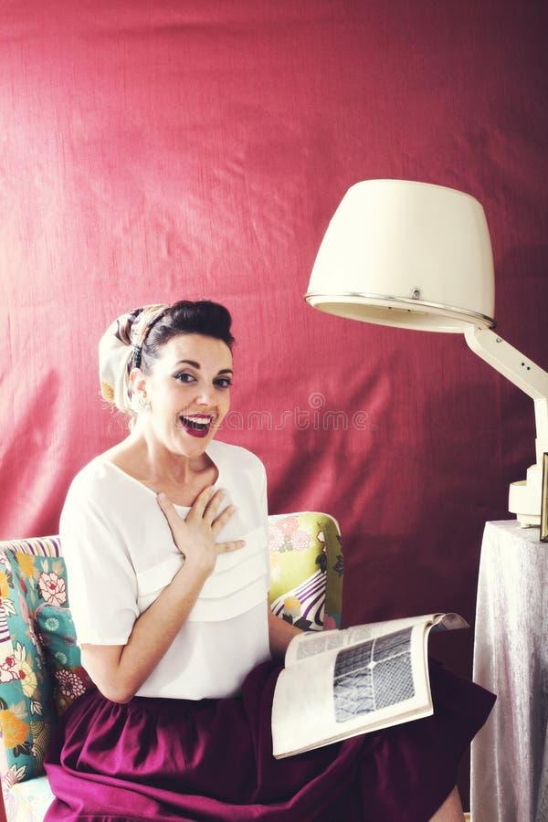 Weinlesehausfrau liest Zeitschrift in einem Schönheitssalon lizenzfreies stockbild
