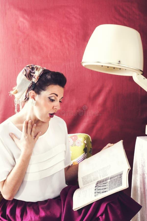 Weinlesehausfrau liest Zeitschrift im Schönheitssalon lizenzfreie stockbilder