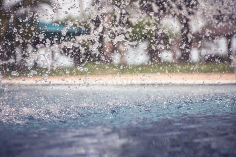 Weinlesehintergrund mit freezed Wasser fällt, nachdem er im Swimmingpool auf Wasseroberfläche während des Regens mit unscharfem b lizenzfreie stockfotografie