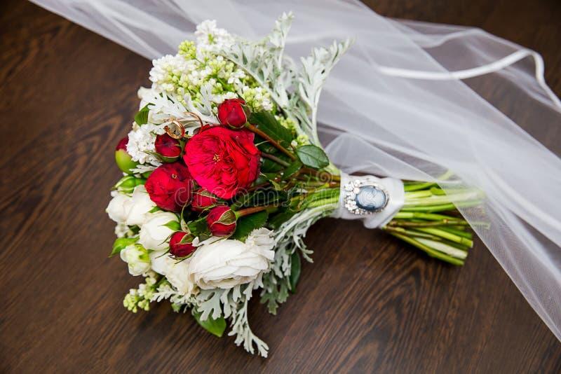 Weinlesehochzeitsblumenstrauß mit Ringen und Schleier lizenzfreie stockbilder