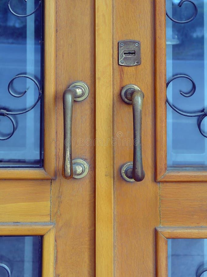 Weinleseholztür mit zwei großen Metallgriffen und geschmiedetes Gitter auf Vorderansicht der Fenster stockfotos
