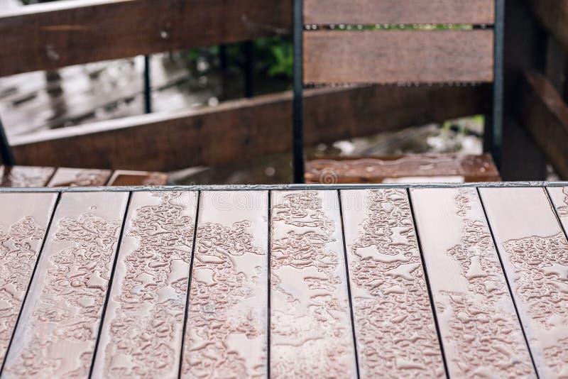 Weinleseholztisch und -stuhl für machen eine Pause auf Bretterboden nahe See Häuschen im Wald nahe Fluss mit großer Terrasse lizenzfreie stockfotografie