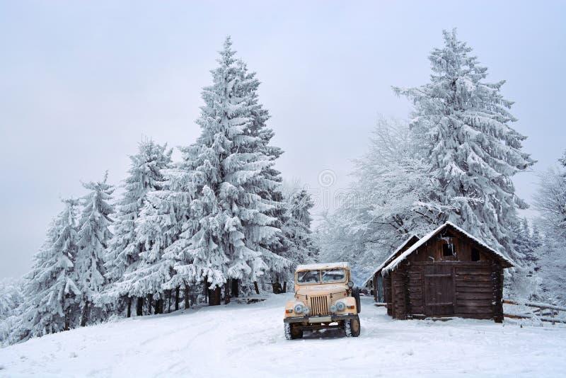 Weinlesejeep im Winterwald stockfotografie