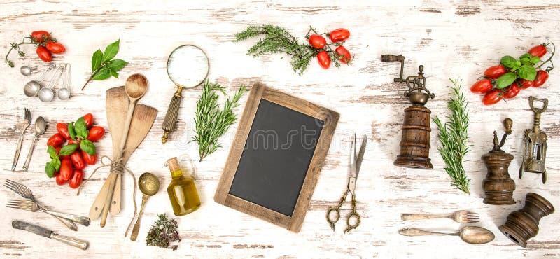 Weinleseküchengeräte mit roten Tomaten und Kräutern lizenzfreie stockbilder