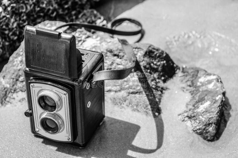 Weinlesekamera auf Strand in Schwarzweiss lizenzfreie stockfotografie