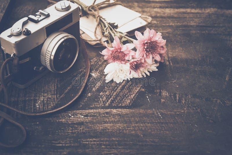 Weinlesekamera mit Blumenstrauß von Blumen auf altem hölzernem Hintergrund stockfoto