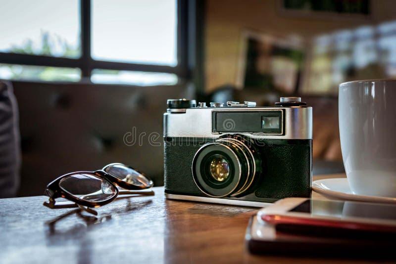 Weinlesekamera mit Kaffeetasse, Gläsern und Smartphone auf dem ta stockfoto