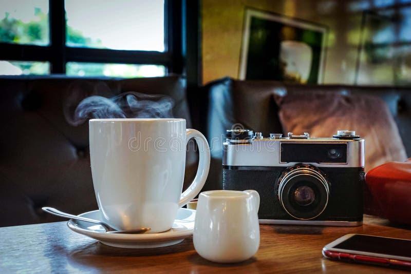 Weinlesekamera mit Kaffeetasse, Gläsern und Smartphone auf dem ta stockfotografie