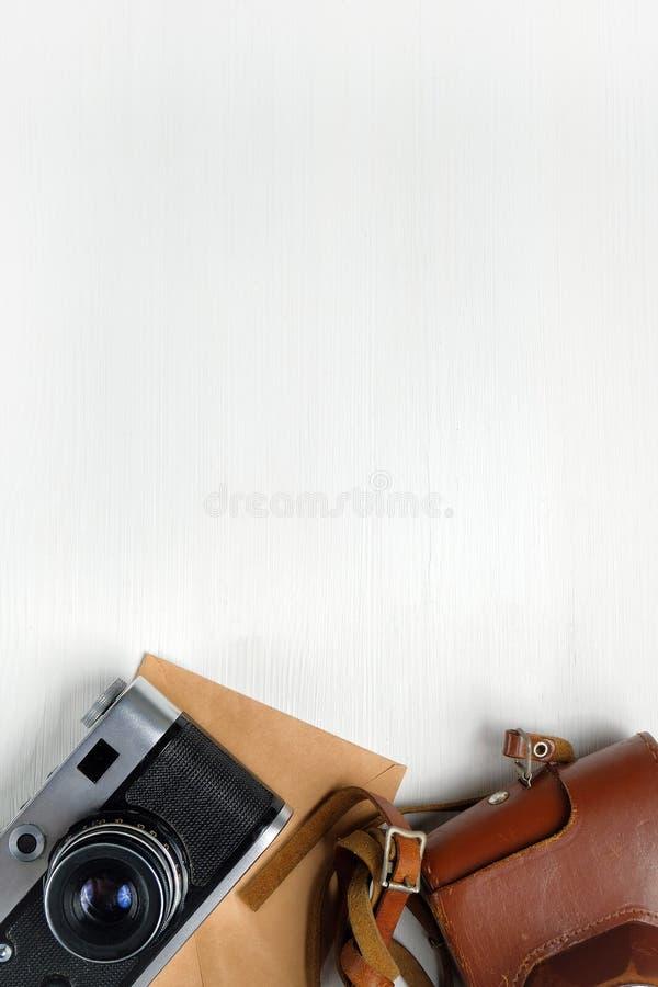 Weinlesekamera mit ledernem Fall- und Kraftpapierumschlag auf einem h?lzernen wei?en Hintergrund Kopieren Sie Platz vertikal geto stockfoto