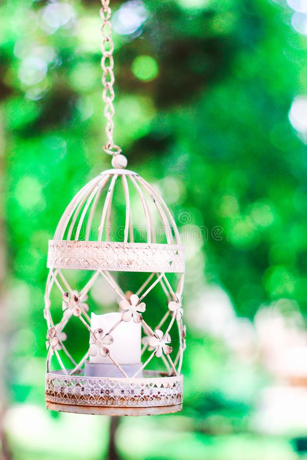 Weinlesekerze im dekorativen Vogelkäfig Weißer Birdcage auf Blumenhintergrund Hochzeitsdekoration, grünes Laub und Laterne stockfotos