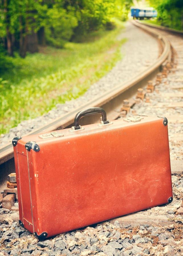 Weinlesekoffer auf der Eisenbahn, blauer Zug ist aus lizenzfreies stockfoto