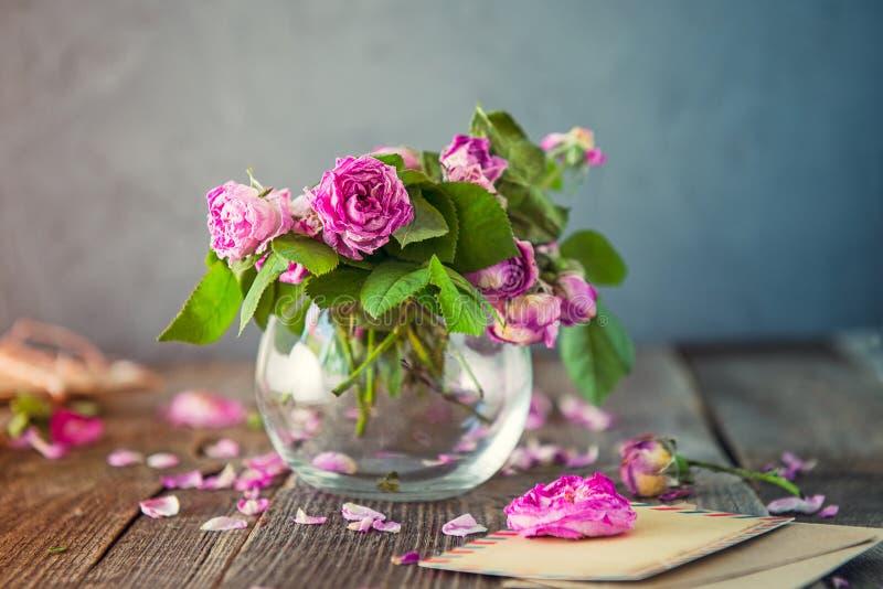Weinlesekonzept - Blumenstrauß von verwelkenden Teerosen im Glasvase, alte Buchstaben in den Kraftpapierumschlägen, leere Grußkar stockfoto