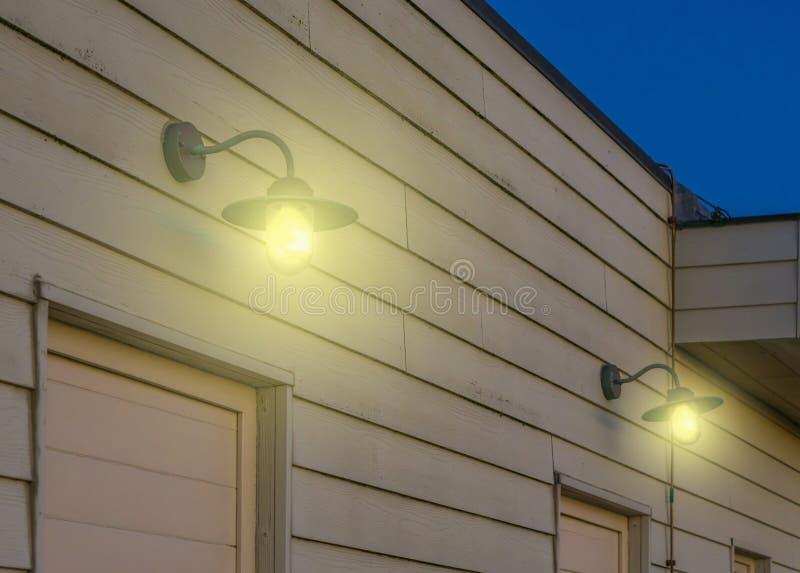 Weinleselaternen, die an einer hölzernen Wand eines Weinlesehauses, Beleuchtung im Freien im Retrostil, Lampen glänzen Licht in d stockfotografie