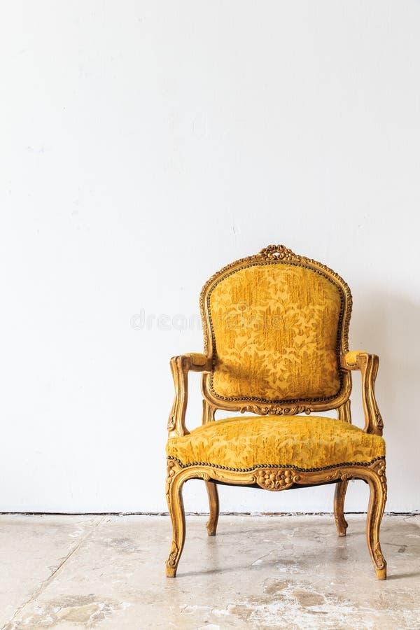 Weinleselehnsessel auf weißer Wand lizenzfreie stockbilder