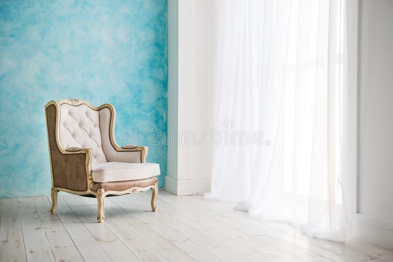 Weinleselehnsessel gegen weiße Wand und großes Fenster mit Vorhang Platz für Ihr Exemplar lizenzfreie stockfotos