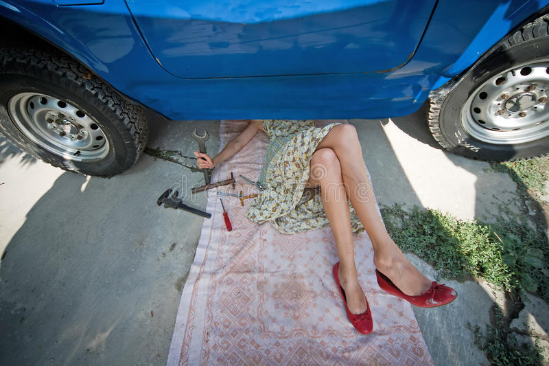 Weinlesemädchen mit Hilfsmitteln unter Auto lizenzfreie stockbilder