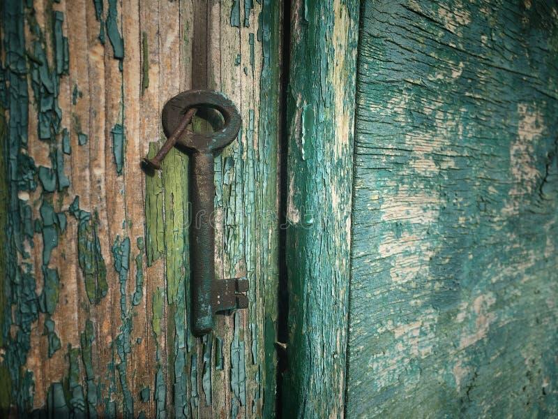 Weinlesemessingschlüssel auf der hölzernen Wand fest auf rostigem Nagel lizenzfreie stockfotos