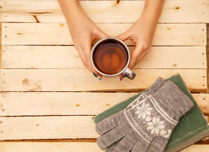 Weinlesemetallbecher in den weiblichen Händen Es gibt auch ein Weinlesebuch, einen Fichtenzweig und gestrickte Handschuhe auf dem lizenzfreie stockfotografie