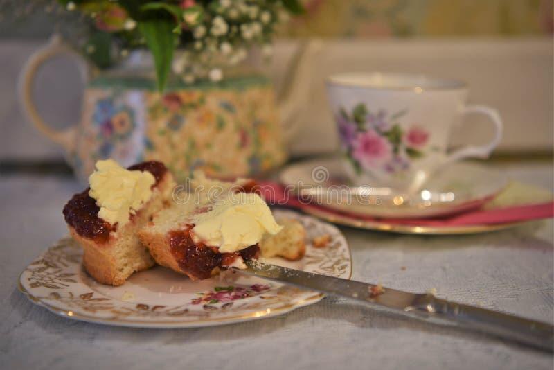 Weinlesenachmittagstee mit Blumentonware und Scone mit Sahne und Stau stockfotos