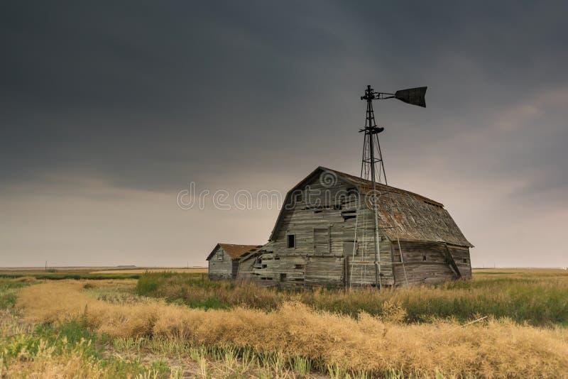 Weinlesescheune, -behälter und -windmühle unter ominösen bewölkten Himmeln in Saskatchewan, Kanada lizenzfreie stockbilder