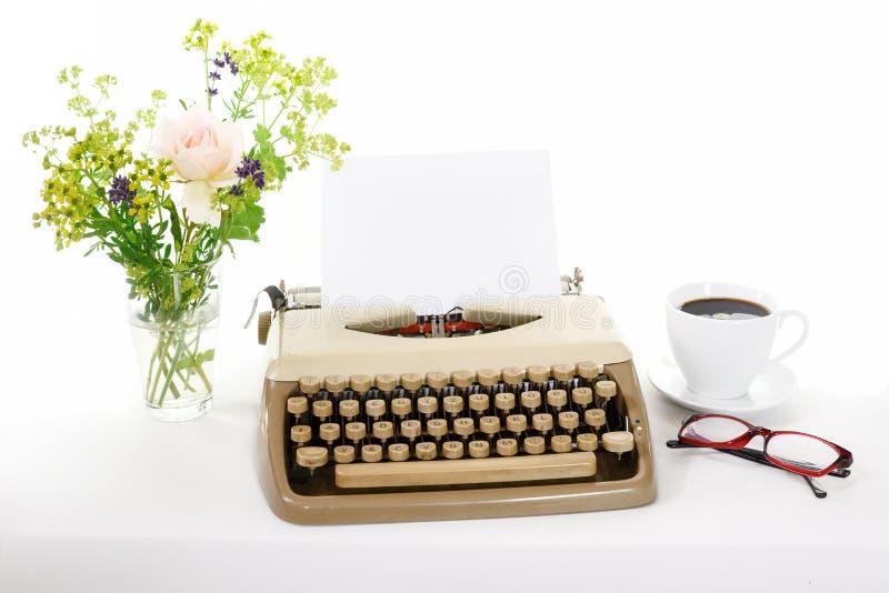 Weinleseschreibmaschine von den fünfziger Jahren mit leerem Papier, Blumen Kaffee und Gläsern auf einer weißen Tabelle, Kopienrau lizenzfreie stockbilder