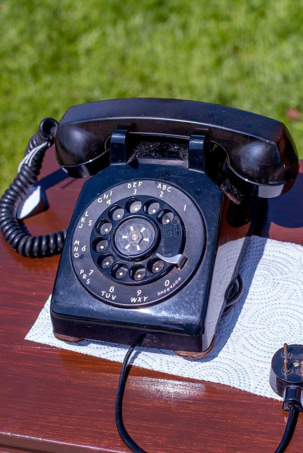 Weinleseschwarz-Drehtelefon auf einem Schreibtisch lizenzfreies stockbild