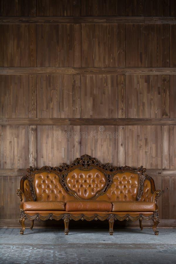 Weinlesesofa nahe hölzerner Wand lizenzfreie stockfotografie