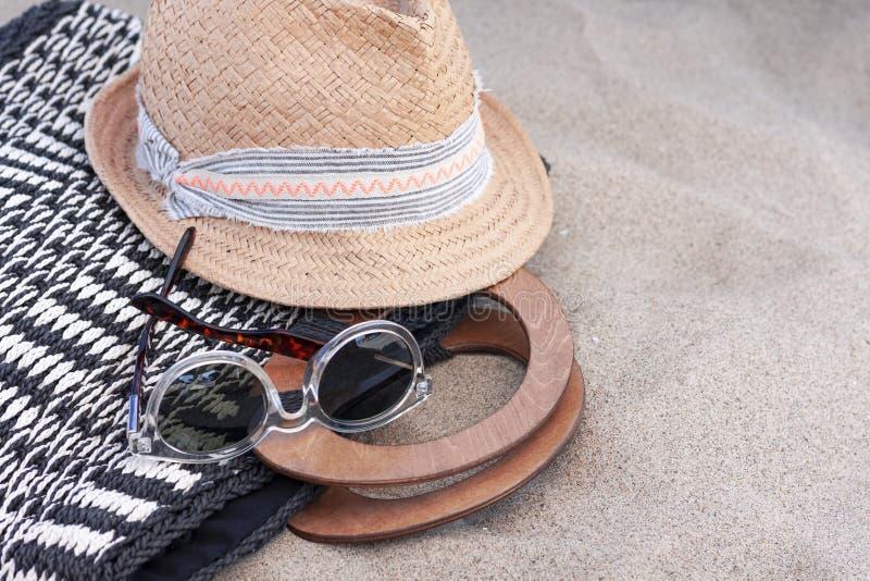 Weinlesesommerhut, Strandweidentasche und Sonnenbrille auf dem Strand lizenzfreies stockbild