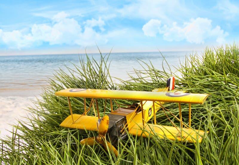 Weinlesespielzeugflugzeug im hohen Gras am Strand stockbilder