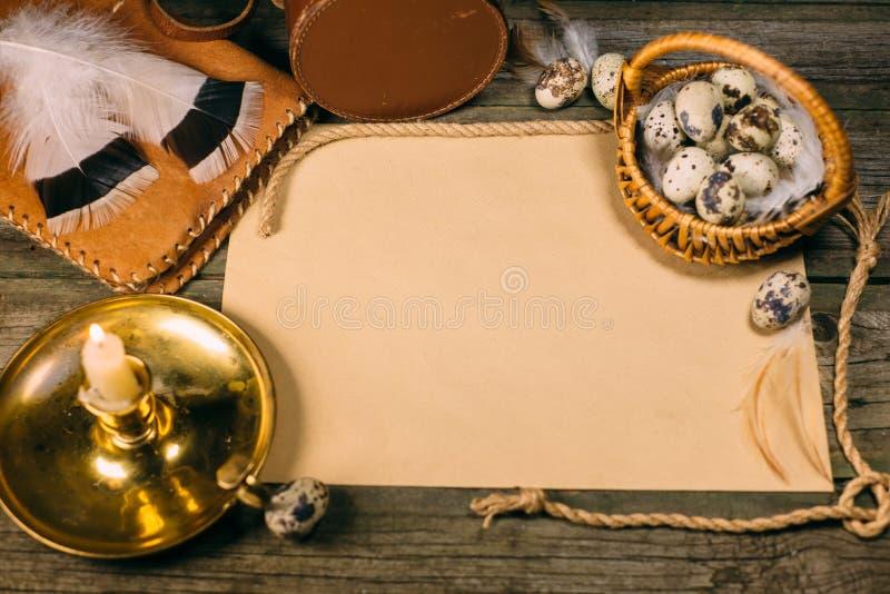 Weinlesespott oben Messingkerzenleuchter mit brennender Kerze, Weinlesegegenständen und gelbem Papier für Text auf rustikalem höl lizenzfreie stockbilder