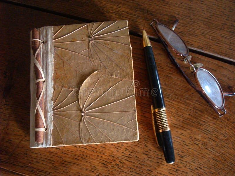 Weinlesestift, Gläser und handgemachtes Notizbuch auf einer Holzoberfläche lizenzfreie stockfotos