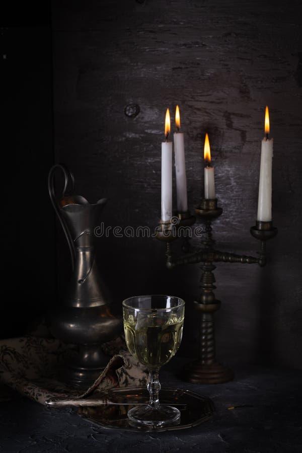 Weinlesestillleben mit einem Glas Wein und Kerzen stockbild