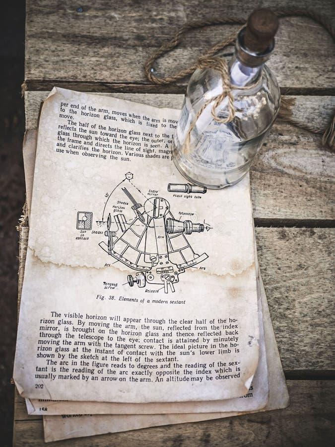 Weinlesestillleben mit Sextantbild in einem alten Buch und in einer leeren Glasflasche mit Seil auf gealtertem hölzernem Hintergr lizenzfreies stockbild