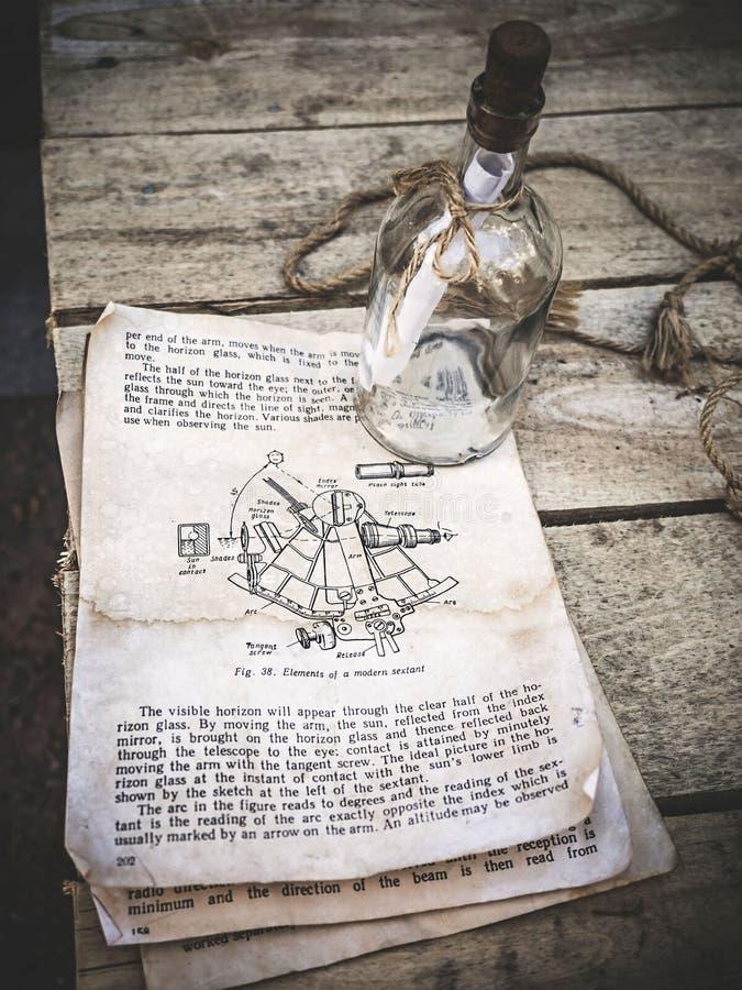 Weinlesestillleben mit Sextantbild in einem alten Buch und in einer leeren Glasflasche mit Seil auf gealtertem hölzernem Hintergr stockfotografie
