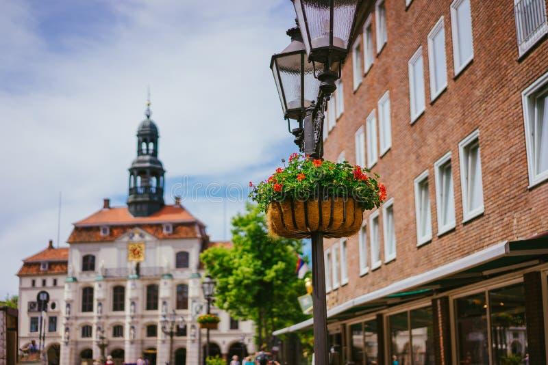 WeinlesestraßenlaterneLaterne mit Blumenbeet Historisches Rathaus auf dem Hintergrund in Lueneburg Deutschland lizenzfreies stockfoto