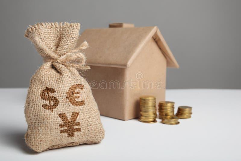 Weinlesetasche mit Dollar-, Euro- und Yuanzeichen und gelben Münzen auf dem Hintergrund der Handwerkszahl des Hauses Steuern Sie  stockbild