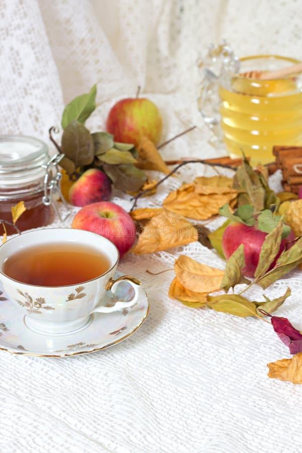 Weinleseteeparty - Teeschalen, -äpfel und -honig auf weißem Holztisch lizenzfreie stockfotografie