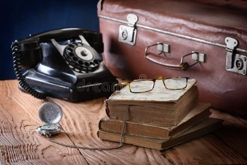Weinlesetelefon, Koffer, Uhren und alte Bücher stockbild