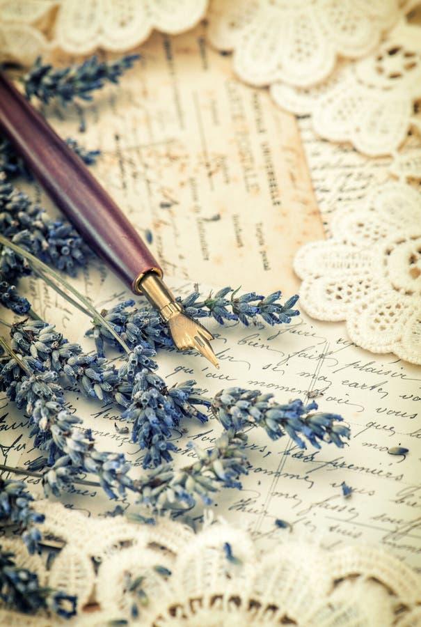 Weinlesetintenstift, getrocknete Lavendelblumen und alte Liebesbriefe stockfotos