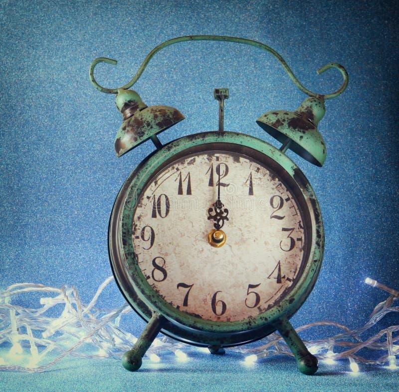 Weinleseuhr über blauem Eis bokeh Hintergrund und weißer Girlande Konzept des neuen Jahres Selektiver Fokus stockfoto