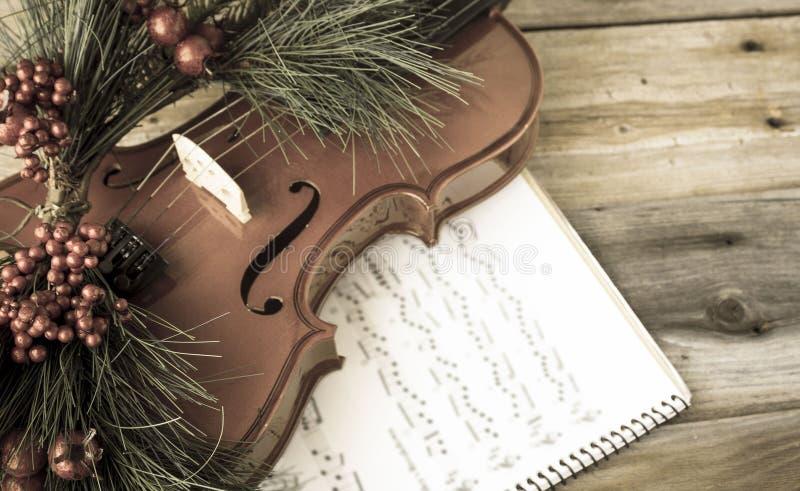 Weinlesevioline schmückte mit dem Weihnachtsfarn, der auf Noten liegt lizenzfreies stockfoto