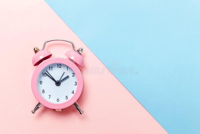 Weinlesewecker lokalisiert auf blauem und rosa Pastellhintergrund stockfotografie