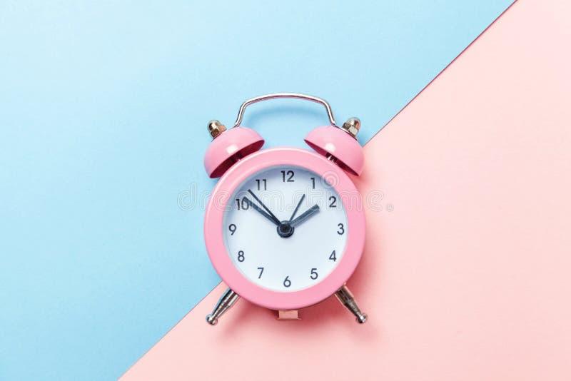 Weinlesewecker lokalisiert auf blauem und rosa Pastellhintergrund stockfoto